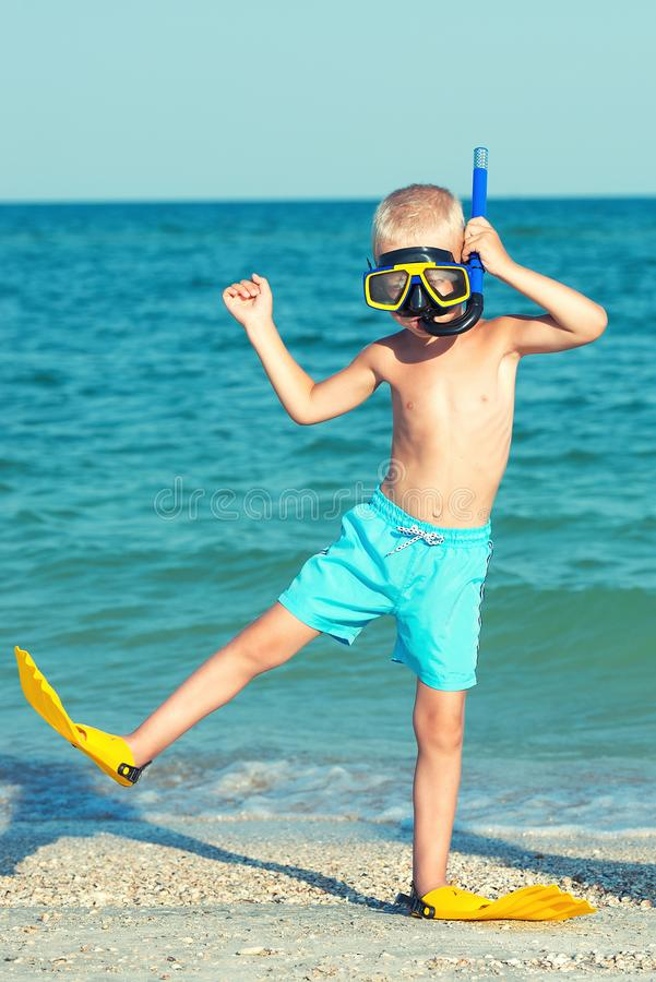 Boy in masks and fins are going to dive into the sea. Small diver. royalty free stock images
