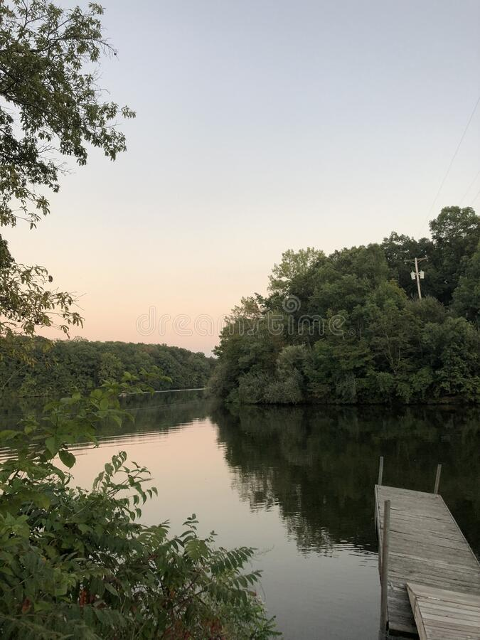 Small dock on a natural lake and river with multicolor sunset stock photo