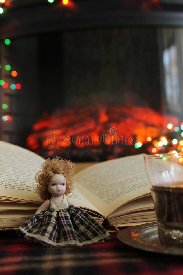 A small doll, an open book and a Cup of Cai on the background of a burning fireplace and Christmas lights, garlands royalty free stock images
