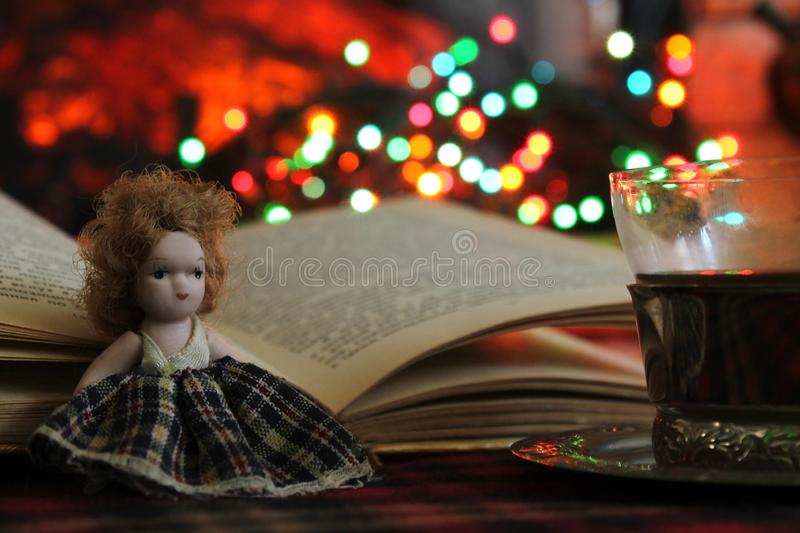A small doll, an open book and a Cup of tea on the background of a burning fireplace and Christmas lights, garlands. A small doll, an open book and a Cup of tea stock photos