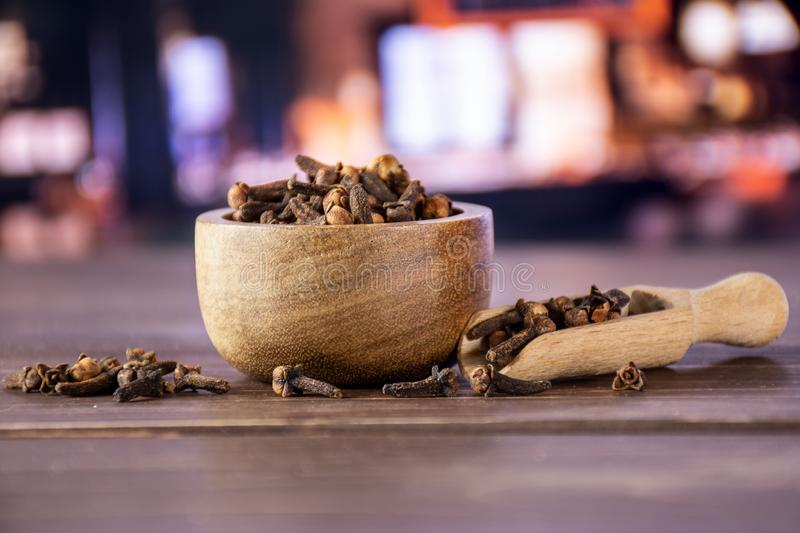 Small dried cloves spice with restaurant. Lot of whole small dried cloves spice scoop with wooden bowl with restaurant in background stock images