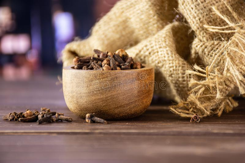 Small dried cloves spice with restaurant. Lot of whole small dried cloves spice textil with wooden bowl with restaurant in background royalty free stock images