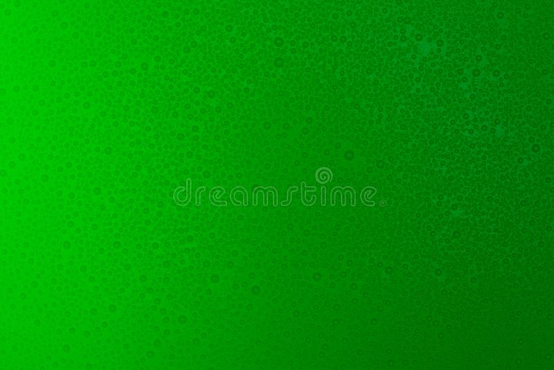 Small droplets of water on a green, matte background illuminated with a delicate light. Small droplets of water on a green, matte background illuminated with a stock images