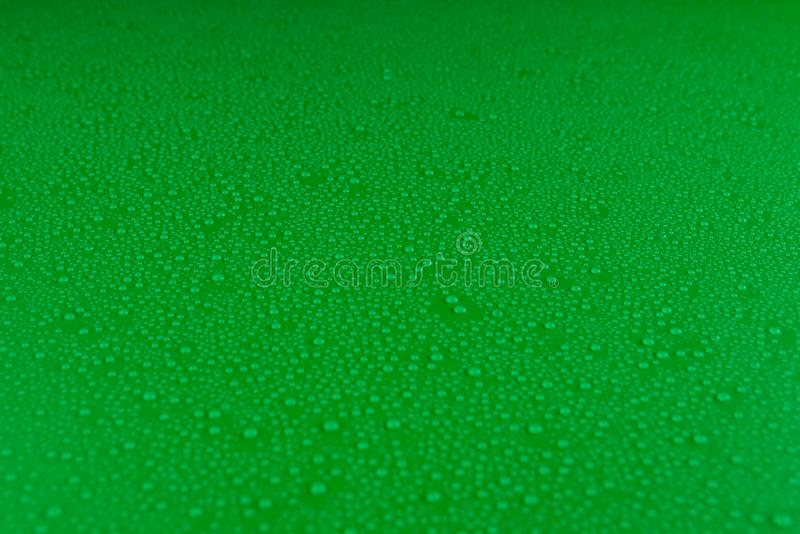 Small droplets of water on a green, matte background illuminated with a delicate light. Small droplets of water on a green, matte background illuminated with a stock photo