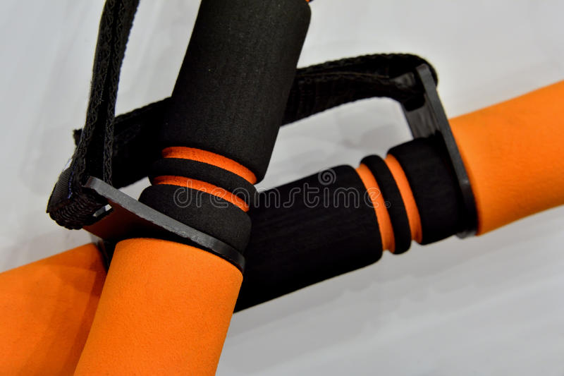 Small dumbbell with bright color. A pair of small dumbbell with bright orange color, shown as sport facilities for kinds of people stock photography