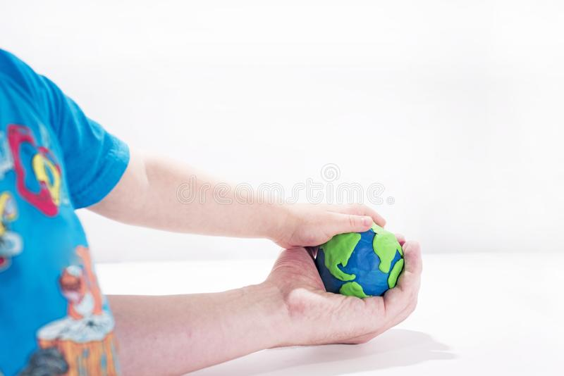 Small Earth model with human hands. Abstract composition of peace royalty free stock photos