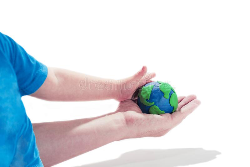 Small Earth model with human hands. Abstract composition of peace stock image