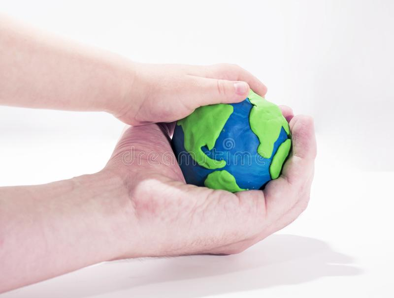 Small Earth model with human hands. Abstract composition of peace royalty free stock image