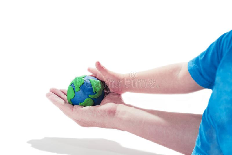 Small Earth model with human hands. Abstract composition of peace royalty free stock photography