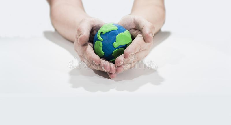 Small Earth model with human hands. Abstract composition of peace royalty free stock photo