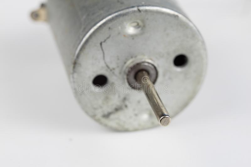 Small electric motor on a white workshop table. Electric drive u. Sed in small electrical devices. Light background stock photo