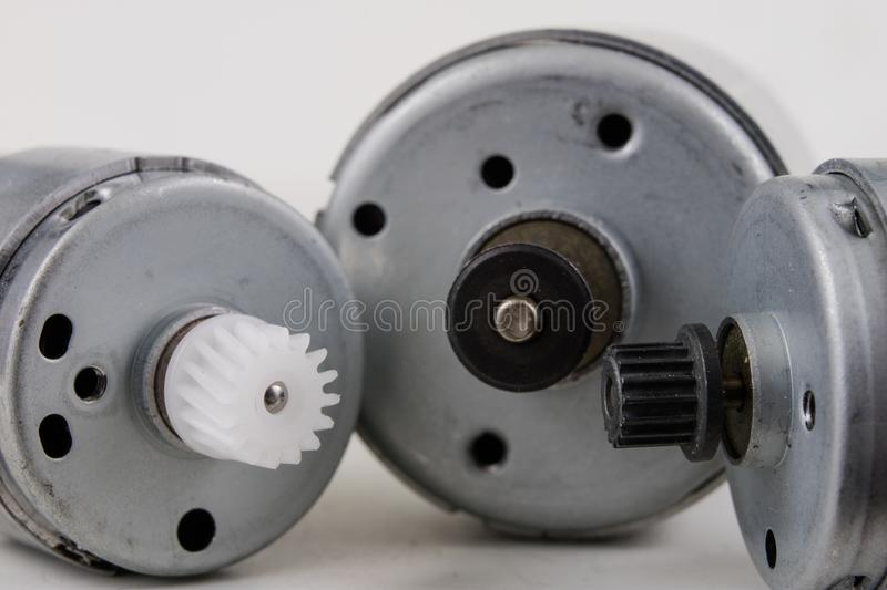 Small electric motor on a white workshop table. Electric drive u. Sed in small electrical devices. Light background stock image