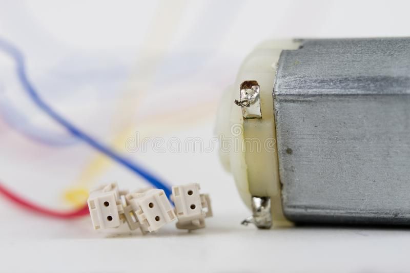 Small electric motor on a white workshop table. Electric drive u. Sed in small electrical devices. Light background royalty free stock images
