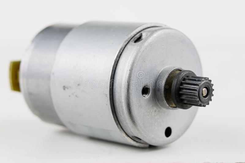 Small electric motor on a white workshop table. Electric drive u. Sed in small electrical devices. Light background royalty free stock photography