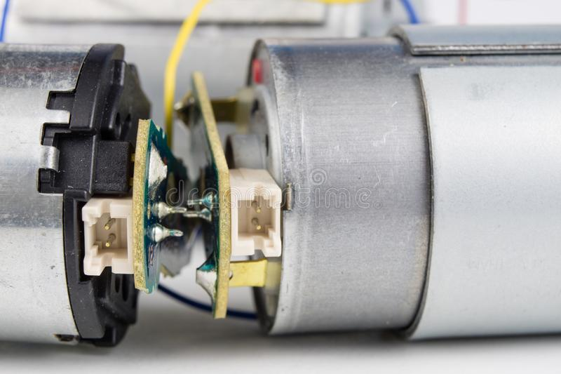 Small electric motor on a white workshop table. Electric drive u. Sed in small electrical devices. Light background stock photos