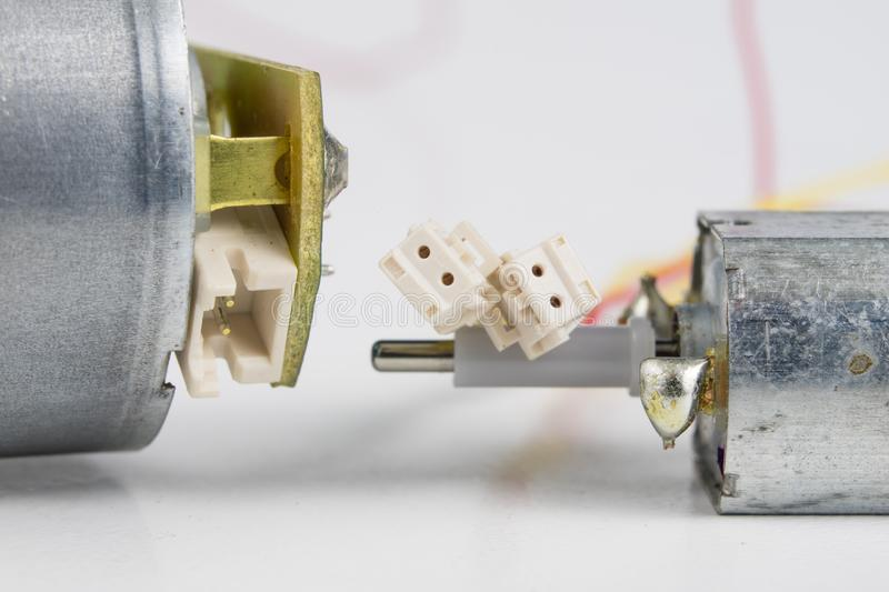 Small electric motor on a white workshop table. Electric drive u. Sed in small electrical devices. Light background stock photography
