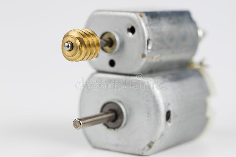Small electric motor on a white workshop table. Electric drive u. Sed in small electrical devices. Light background stock images