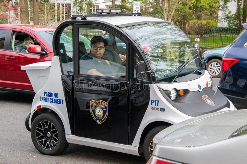 A small electric smart car Gem made by Polaris is seen being used as a parking enforcement vehicle by a Princeton Police Officer. Princeton, New Jersey - April royalty free stock photos