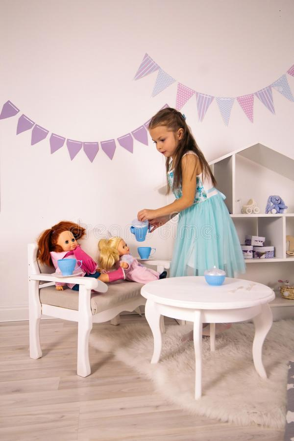 elegant caucasian girl in a blue dress play with dolls, tea party with toys royalty free stock images