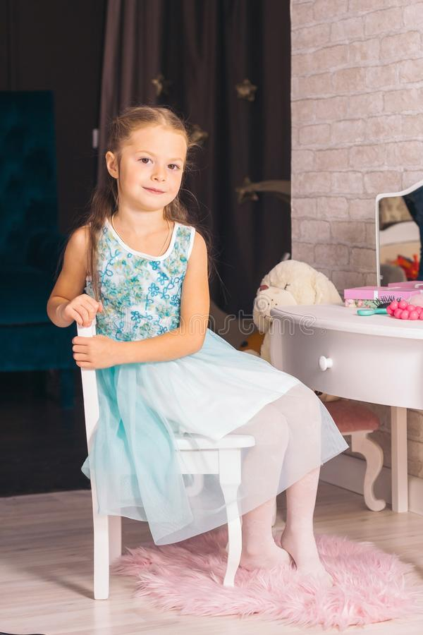 Elegant caucasian girl sits on a chair near the dressing table and looking in the camera. Small elegant caucasian girl sits on a chair near the dressing table royalty free stock images