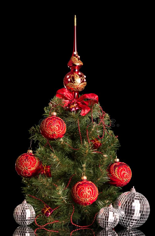 Small elegant Christmas tree decked out for the holiday, next mirrored toys-balls, isolated on black. Background stock photos