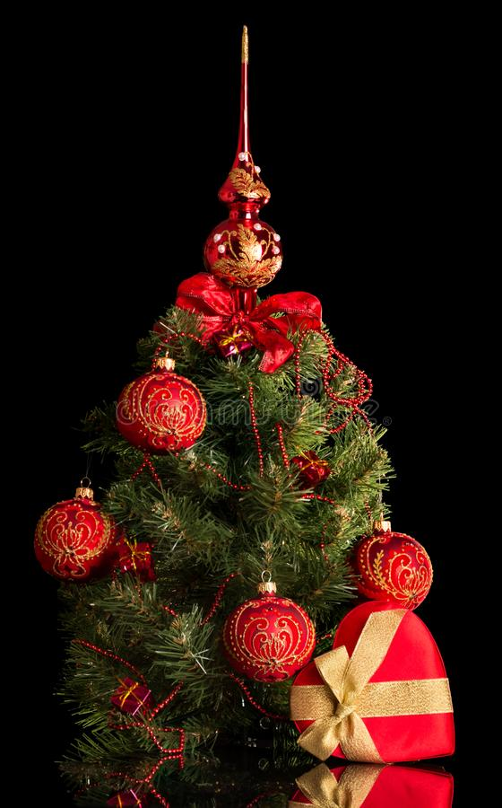 Small elegant Christmas tree decorated with baubles and beads next to the heart, isolated on black. Background stock photo