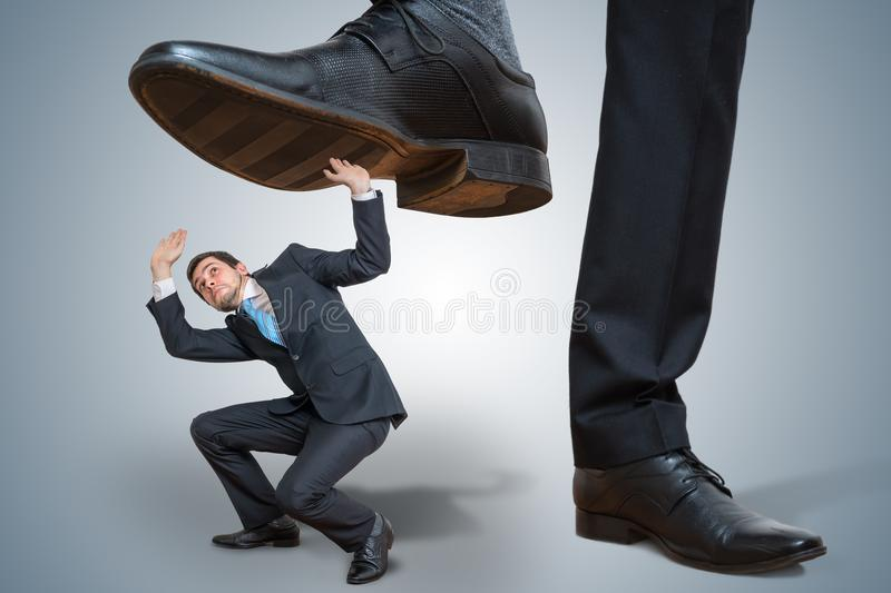 Small employee is abused by big boss stock images