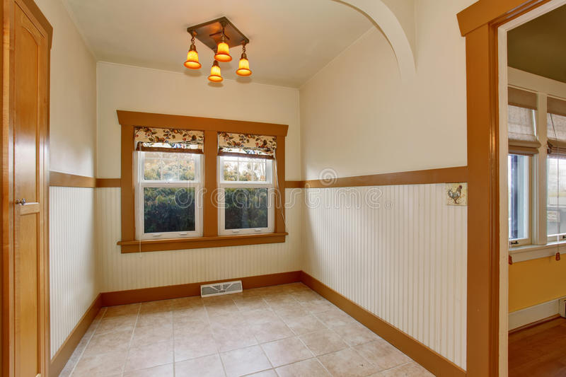 Small empty dining room interior in old craftsman style home. White room with bown trim, tile floor and one window stock photos