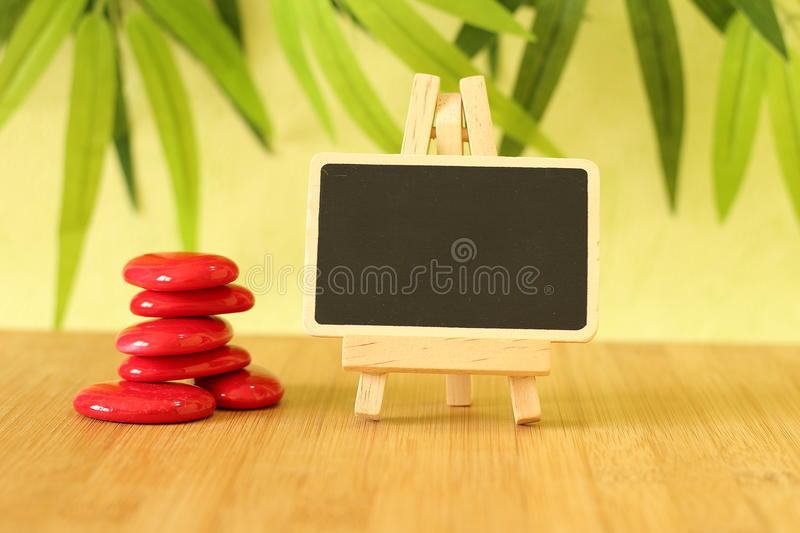Small empty slate in width to write a message that is posed on an easel with zen lifestyle red stones all on wooden floor and gre stock photos
