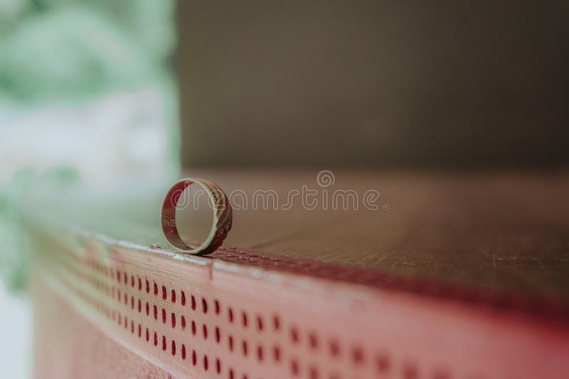 Small engagement golden ring on red surface royalty free stock images