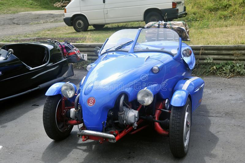 Small English three-wheeled car. At the foot of the Puy de Sancy stock photography