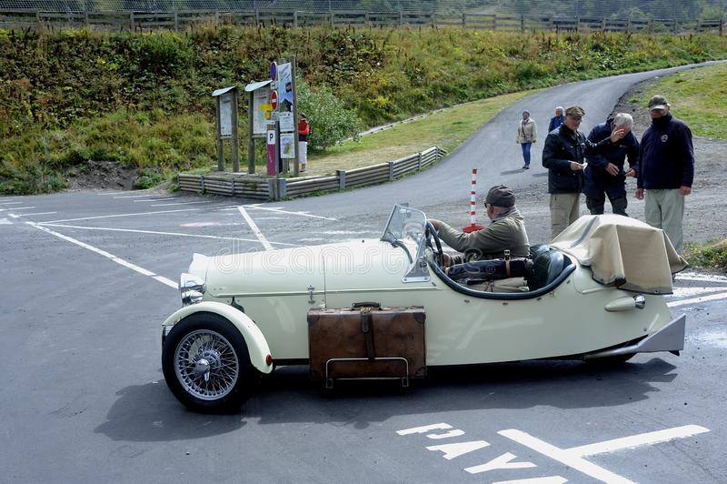 Small English three-wheeled car. At the foot of the Puy de Sancy royalty free stock photo