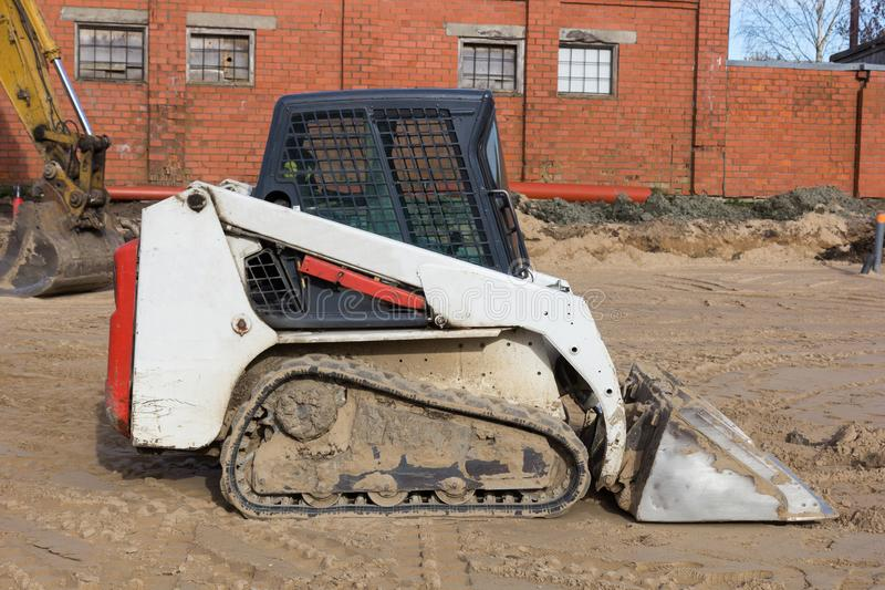 Small excavatot at construction site stock photo