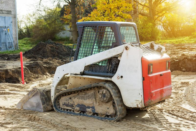 Small excavatot at construction site royalty free stock photo