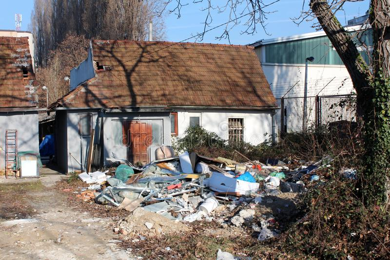 Small family house in shade of tall tree next to industrial complex separated with wire fence surrounded with piles of garbage and royalty free stock image