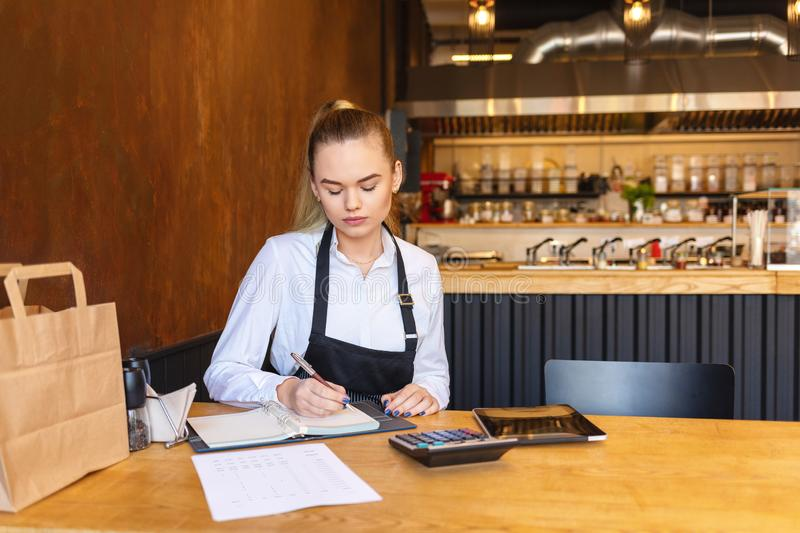 Small family restaurant owner doing finance calculating bills and expenses of small business. – young woman counting profit of store at the end of day stock images