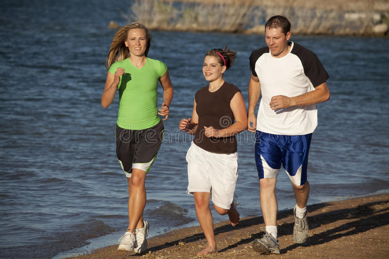 Small family running. A family running and spending time together at the beach exercising and enjoying each other royalty free stock photos