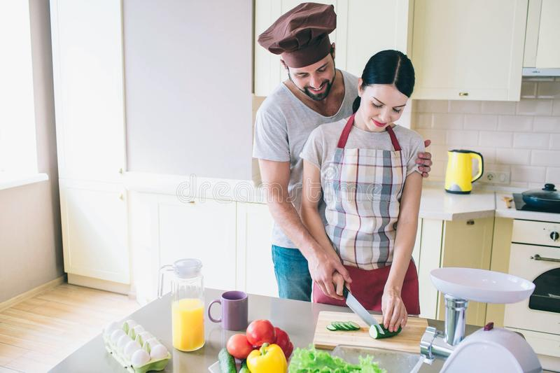 Small family is working together at kitchen. Man and woman cut cucumber together. Guy helps girl to do that. They stock image