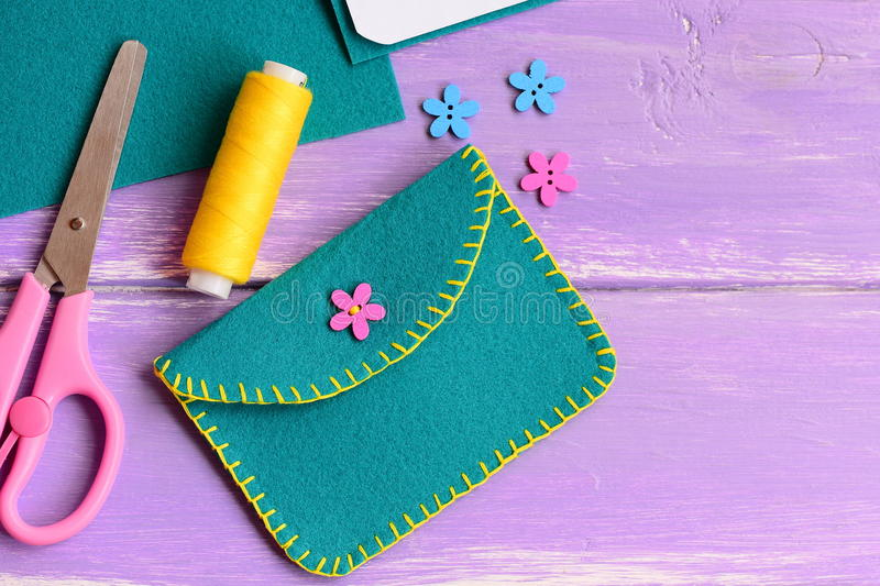 Small felt purse with flower wooden button. Scissors, thread, flower wooden button on a wooden background. Purse sewing pattern. Purse tutorial. Felt purse royalty free stock photo