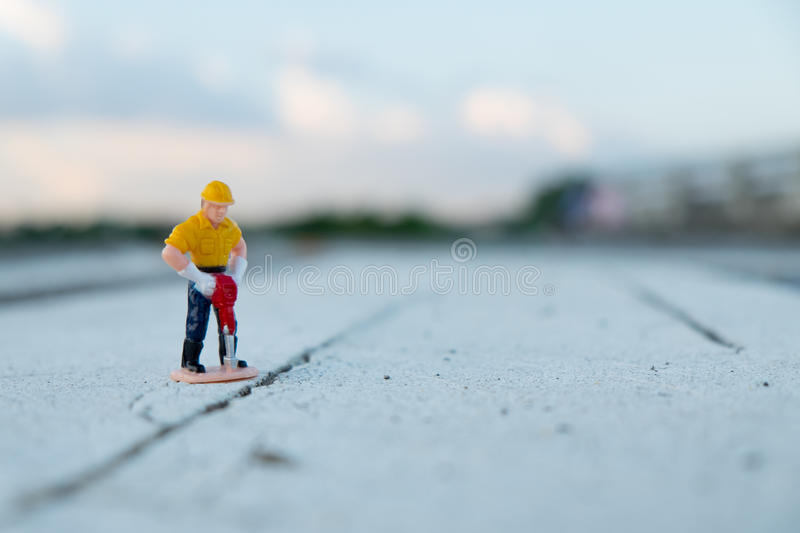 Small figure of a man digging street. Small figure of a man worker digging street royalty free stock images