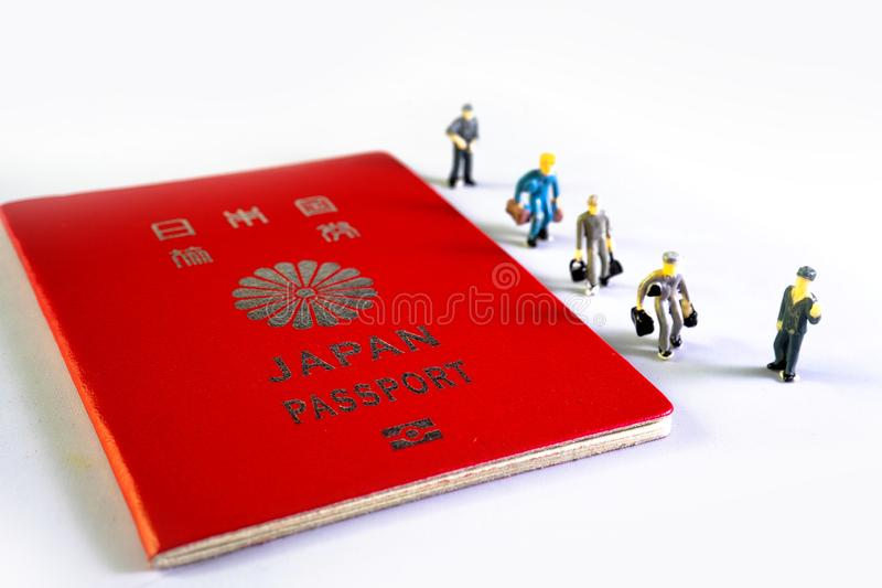Small figure people and Japanese passport. Travel to the country royalty free stock photos