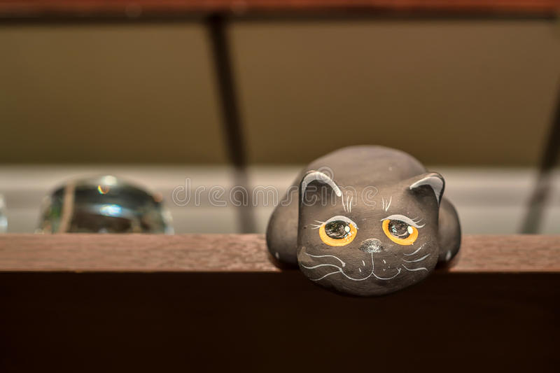 Small figurine of black ct on shelf. Close up cute figurine of black cat with big eyes on shelf stock image