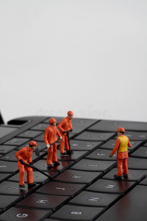 Small figurines of workers repairing computer keyboard royalty free stock images