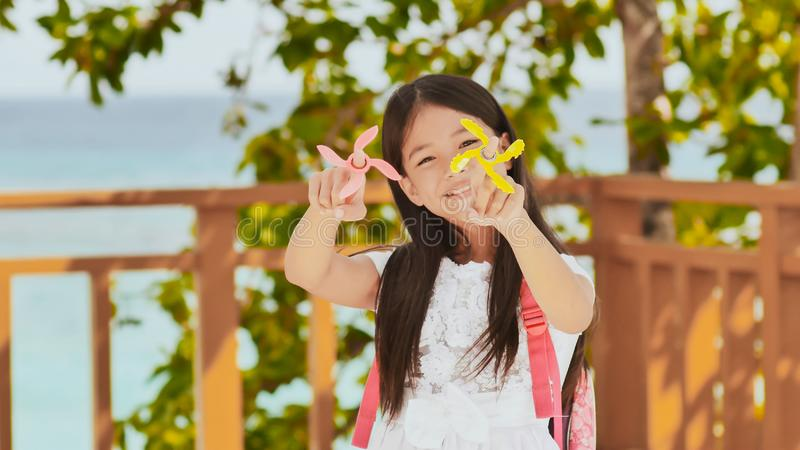 A small filipino schoolgirl shows spinning spinners. Tropical landscape. Summer. Childhood. stock images