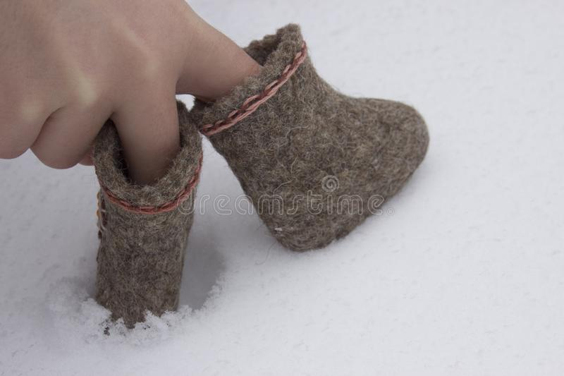 Small fingers hands shod in felt boots coming and falling i. N the white snow royalty free stock photo