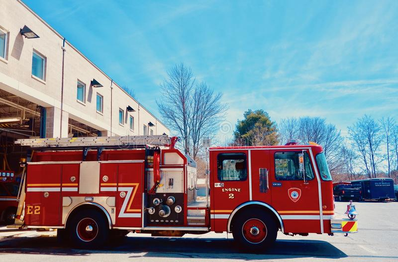 Shiny Red Fire Engine Moving Out of Fire Station, side view. A small fire truck coming out of a fire department building on a bright sunny day, , trees in royalty free stock images