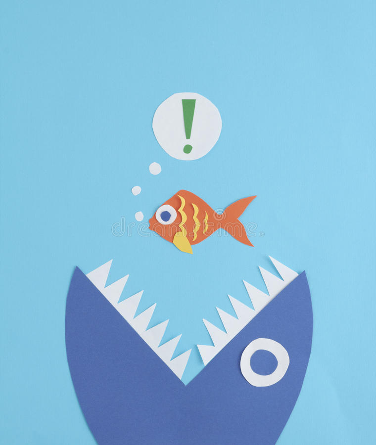 A small fish being eaten by a big fish. A paper cut out scene of a surprised small fish being eaten by a much larger fish from below royalty free stock photo