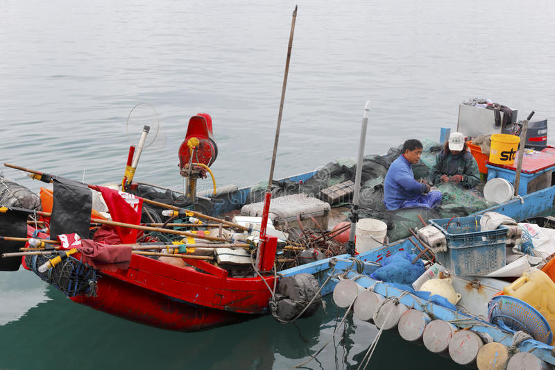 Small fishboat at ferry of yilan county, taiwan. In the morning, fishermen couple finishing seafood caught back, live self-sufficient lives, enviable stock image
