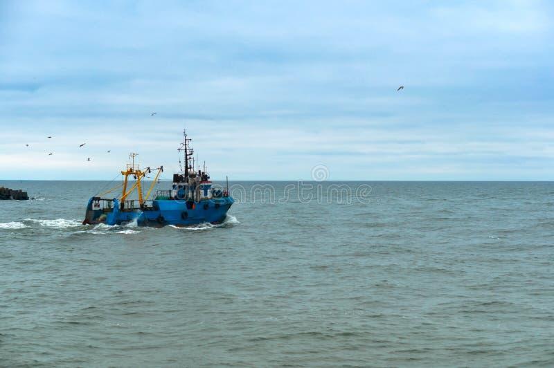 Small fishing boat, small blue ship. Baltic sea, Kaliningrad region, Russia, 3 February 2019 stock photo