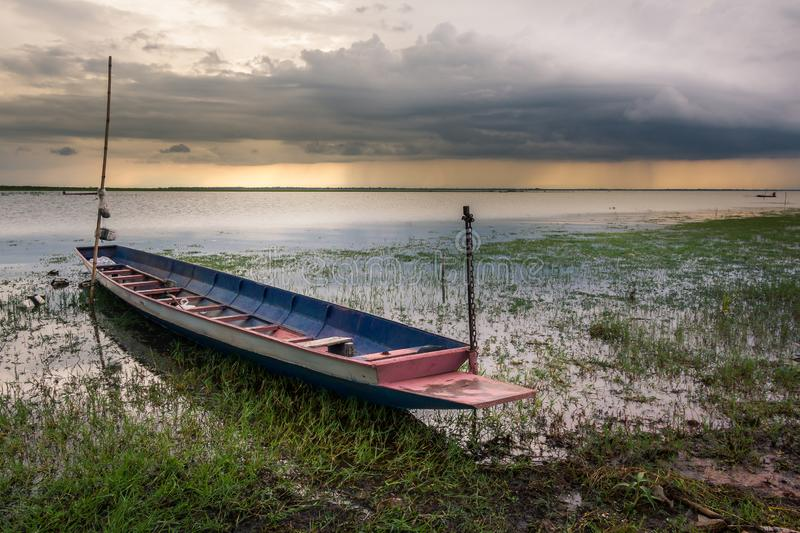 A small fishing boat on the dam. At sunset time royalty free stock photography